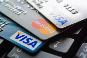 Group of credit cards on computer keyboard with VISA and MasterCard brand logos